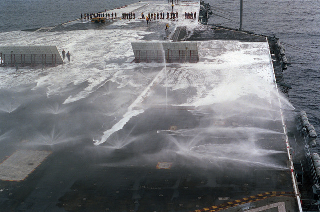 A view of the flight deck of the nuclear-powered aircraft carrier USS DWIGHT D. EISENHOWER (CVN 69) during a test of the ship's aqueous film-forming foam (AFFF) firefighting system.  Flight deck crewmen are standing by to scrub the deck in the background.  A soap substance is mixed with the AFFF to assist in cleaning the deck