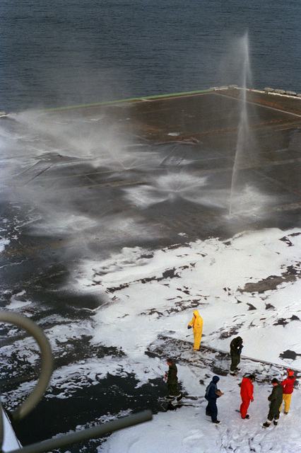 A view of the flight deck of the nuclear-powered aircraft carrier USS DWIGHT D. EISENHOWER (CVN 69) during a test of the ship's aqueous film-forming foam (AFFF) firefighting system.  A soap substance is mixed with the AFFF to assist in cleaning the deck