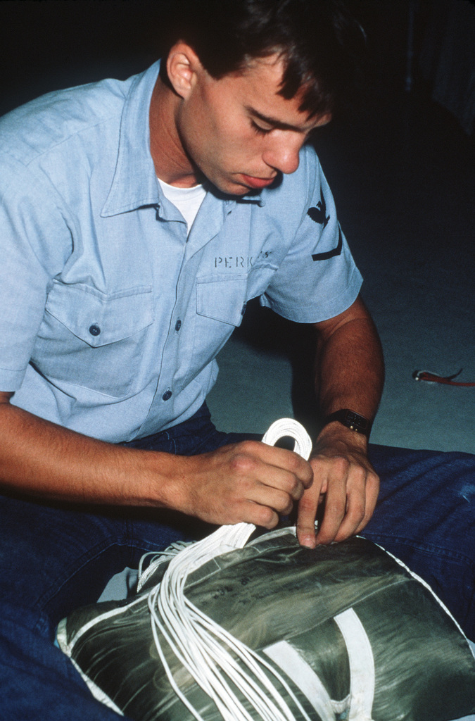An aircrew survival equipmentman repacks a parachute for US Navy test parachutists at the Naval Weapons Center