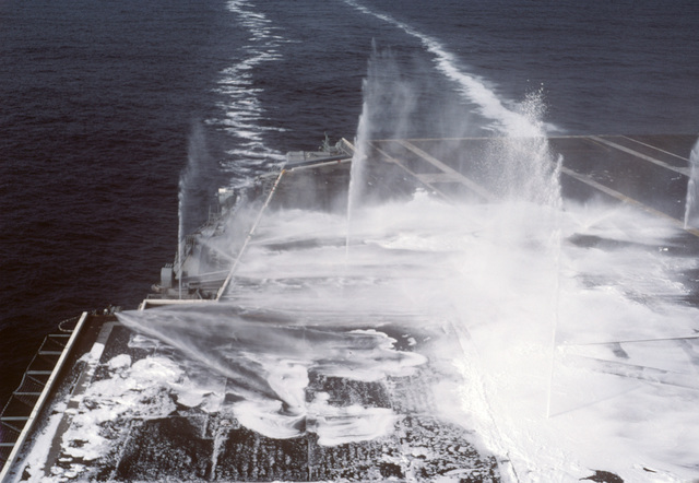 Aqueous film-forming foam (AFFF) sprays from nozzles located in flight deck of the nuclear-powered aircraft carrier USS DWIGHT D. EISENHOWER (CVN 69) during a test of the ship's firefighting system.  A soap substance is mixed with the AFFF to assist in cleaning the deck