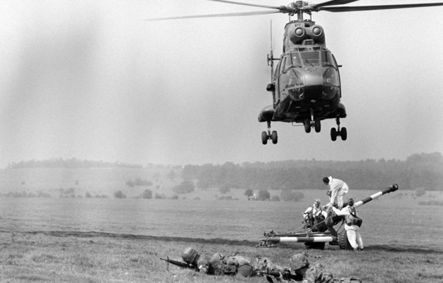 A British SA.330 Puma helicopter hovers over British troops preparing a Howitzer for transport as American infantrymen watch for the enemy during NATO Exercise ARDENT GROUND '87. Members of the Allied Command Europe Mobile Force from Belgium, the Netherlands, West Germany, Italy, Luxembourg, the United Kingdom and the United States are participating in the live artillery/air exercise being staged on Salisbury Plain Training Area in Wiltshire