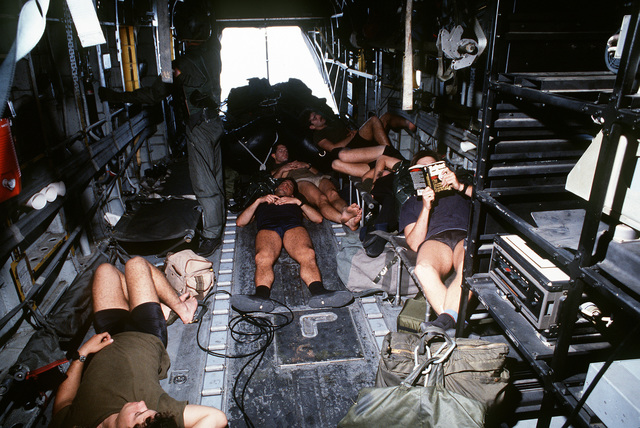 Sea-Air-Land team members rest while in flight aboard a 20th Special Operations Squadron MH-53 helicopter during exercise Solid Shield '87
