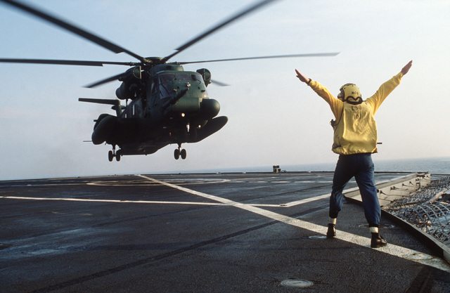 A flight crewman directs a 20th Special Operations Squadron MH-53 helicopter onto the helipad of the amphibious command ship USS MOUNT WHITNEY (LCC 20) during Exercise SOLID SHIELD'87