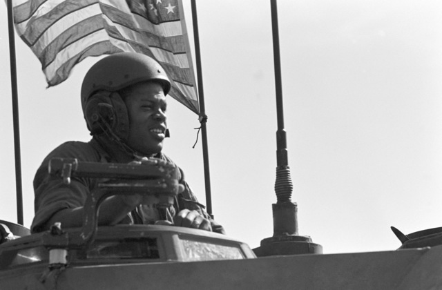 A Marine navigates from the turret of an LVTP7 tracked landing vehicle during an amphibious assault training exercise being conducted from the amphibious assault ship USS NASSAU (LHA 4)