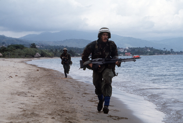 A US Army M60 machine gun crew runs for position while defending Trajillo Beach during Exercise SOLID SHIELD'87