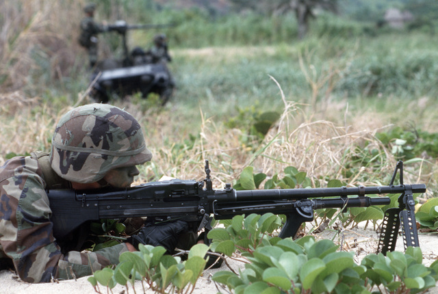 A US Army M60 machine gunner waits for aggressor forces while defending Trajillo Beach during Exercise SOLID SHIELD'87