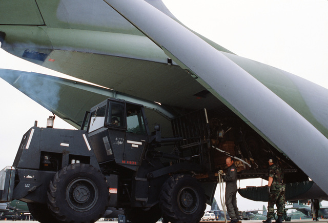 Aerial port personnel from the 446th Military Airlift Wing load a utility trailer onto their C-141 Starlifter aircraft during the ninth international airlift competition Airlift Rodeo'87