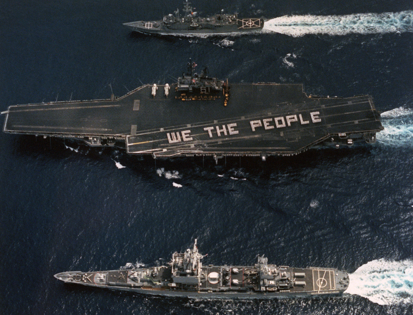 "Crew members form the phrase""We The People""on the flight deck of the aircraft carrier USS RANGER (CV 61) to commemorate the 200th anniversary of the signing of the constitution of the United States.  The Constitution was formally signed on September 17, 1787.  The guided missile cruiser USS LONG BEACH (CGN 9), bottom, and the guided missile frigate USS LEWIS B. PULLER (FFG 23) are accompanying the Ranger"