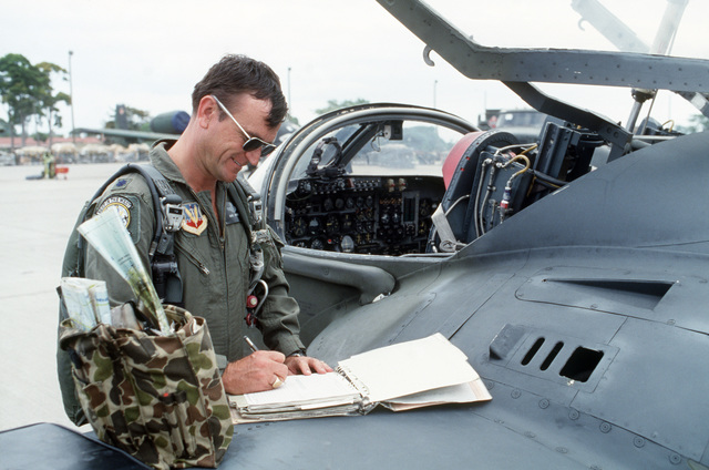 Lieutenant Colonel (LTC) Bud Jackson, 23rd Tactical Air Support Squadron commander, makes an entry in his flight log after completing the 500th OA-37B Dragonfly aircraft mission while deployed in Honduras during Exercise SOLID SHIELD'87