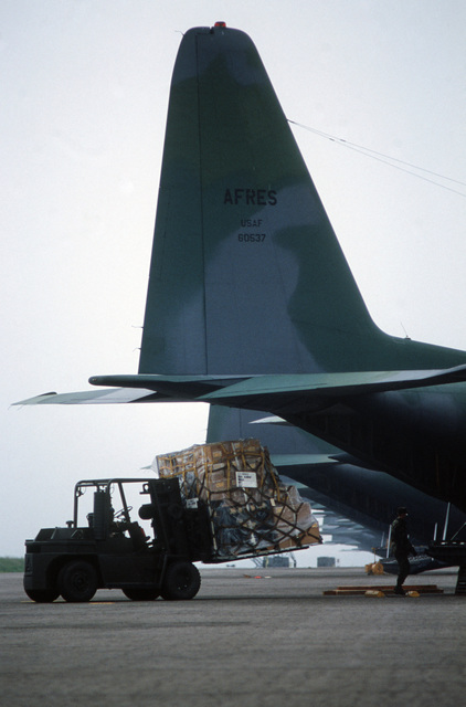 Members of the 34th Mobile Aerial Port Squadron, Air Force Reserve load equipment into a 440th Tactical Airlift Wing C-130A Hercules aircraft for shipment back to the United States during the redeployment phase of Exercise VOLANT PARTNER 87-1.  While in Europe, members of the wing flew airlift missions to 30 air bases in nine NATO nations