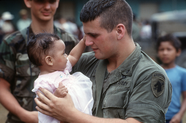 Private First Class (PFC) Russell Reed holds a toddler during Exercise SOLID SHIELD'87.   Reed is assisting A Corps, 1ST Battalion, to distribute school books to the villagers
