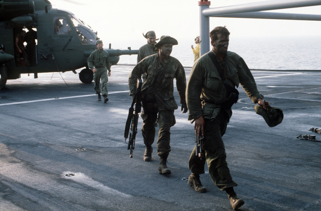 Sea-Air-Land (SEAL) team members head for a mission debriefing after being transported to the amphibious command ship USS MOUNT WHITNEY (LCC 20) aboard a 20th Special Operations Squadron MH-53 helicopter during Exercise SOLID SHIELD'87
