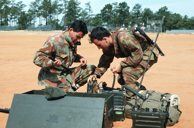 Two Italian combat controllers set up a radio after parachuting into Sicily Drop Zone during the ninth annual international airlift competition Airlift Rodeo'87