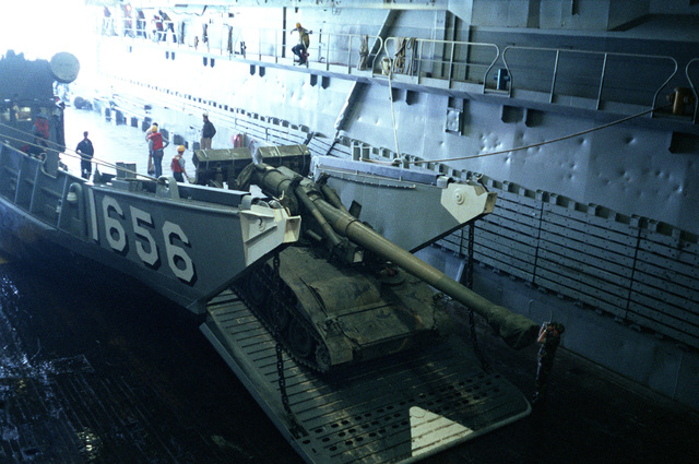 An M110A2 203 mm self-propelled Howitzer is unloaded from the utility landing craft 1656 (LCU 1656) into the docking well of the amphibious transport dock USS TRENTON (LPD 14) during the field training Exercise SOLID SHIELD'87