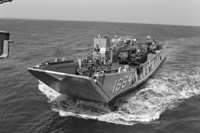 Utility land craft 1664 (LCU 1664) transports two M109A1 155 mm self-propelled Howitzers to the amphibious transport dock USS TRENTON (LPD 14) during field training Exercise SOLID SHIELD'87