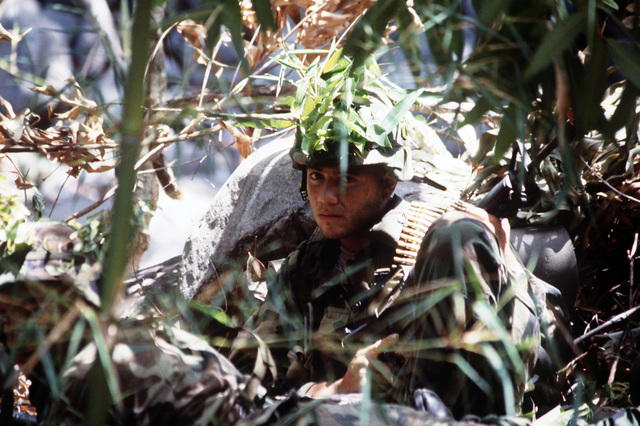 Private First Class (PFC) Hernandez of the 92nd Infantry Brigade, Puerto Rico National Guard, provides security around a campsite during Exercise CAMILLE