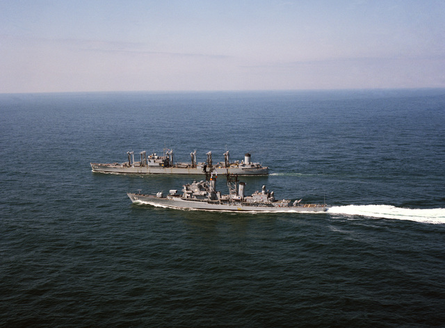 A port view of the guided missile destroyer USS KING (DDG 41) and the fleet oiler USS CALOOSAHATCHEE (AO 98) underway