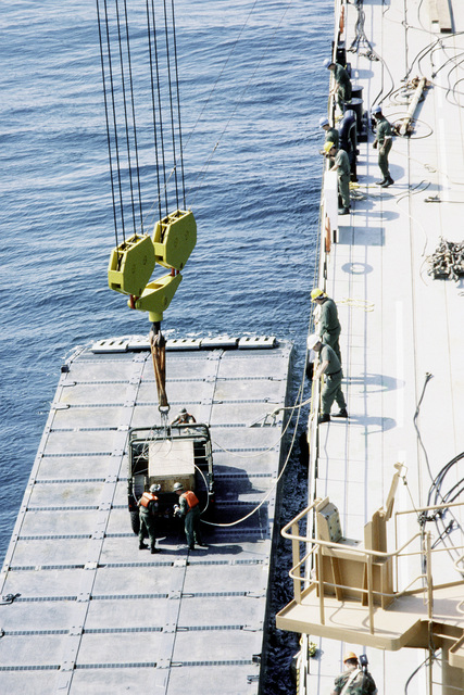 An M998 High-Mobility Multipurpose Wheeled Vehicle (HMMWV) is lowered onto a lighter from the deck of themaritime prepositioning ship SS PFC. EUGENE A. OBREGON. The ship is participating in the first in-stream offload exercise of a maritime prepositioning ship in the open ocean. Equipment and supplies are being unloaded from the ship by the 6th Marine Amphibious Brigade and shuttled to shore by lighter as part of exercise Solid Shield '87