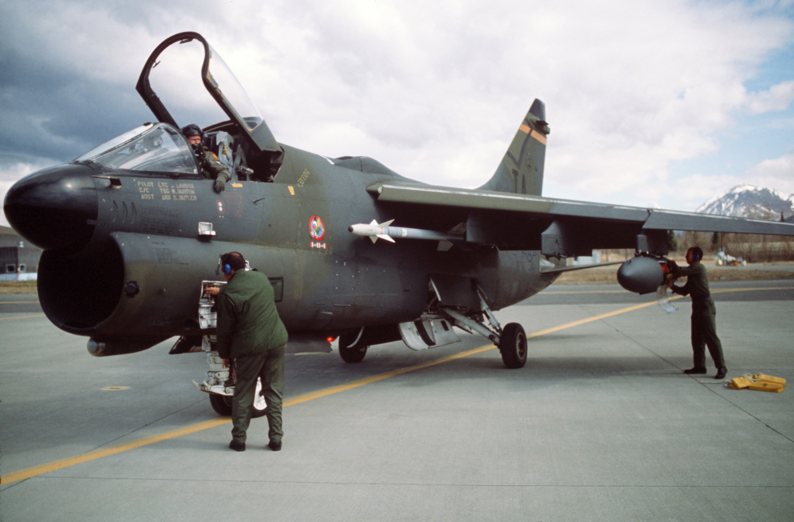 Maintenance technicians work on an A-7D Corsair II aircraft of the 132nd Tactical Fighter Group during Exercise AMALGAM BRAVE'87, an air defense training exercise.  The aircraft is armed with an AIM-9 Sidewinder missile on the fuselage