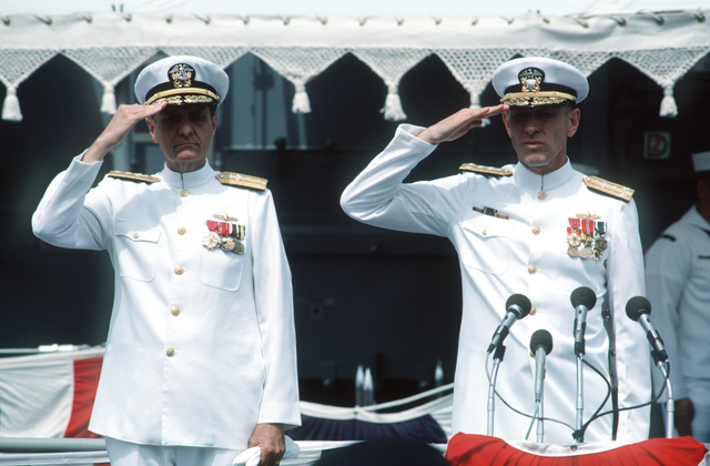 Rear Admiral (RADM) Donald P. Roane, deputy commander, Surface Combatants, Naval Sea Systems Command, left, and Vice Admiral (VADM) George W. Davis Jr., commander Naval Surface Force, US Pacific Fleet, salute the flag during the commissioning of the guided missile frigate USS RODNEY M. DAVIS (FFG 60)