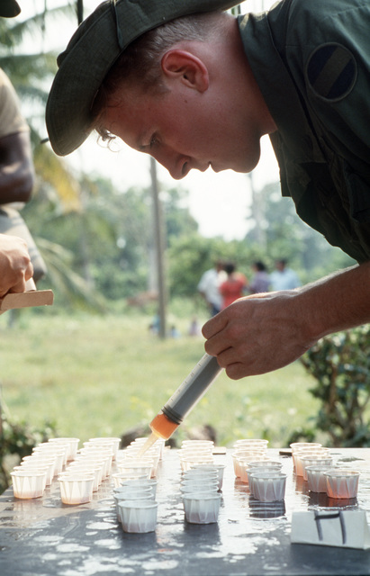 Private First Class (PFC) Terry C. Durham, 675th Medical Detachment, fills paper cups with a deworming medicine for distribution to villagers during a medical readiness training exercise (MEDRETE), part of Exercise SOLID SHIELD'87