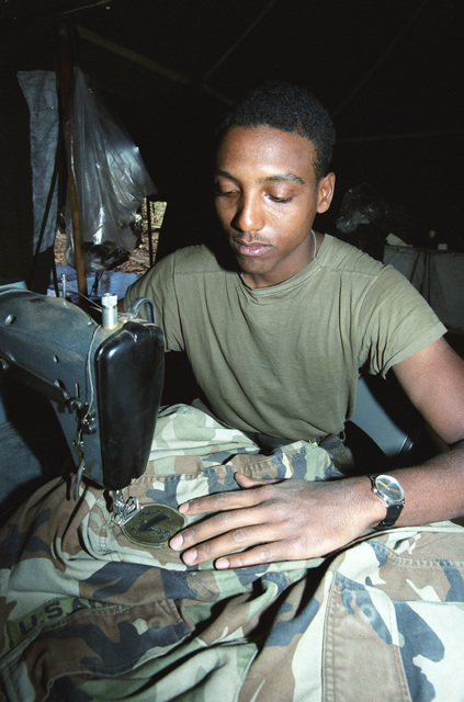 Private First Class (PFC) Richard Lee Taylor, 40th Supply and Service, sews a patch on a uniform during the 21st Infantry Division's annual Army training and evaluation program and field training exercise