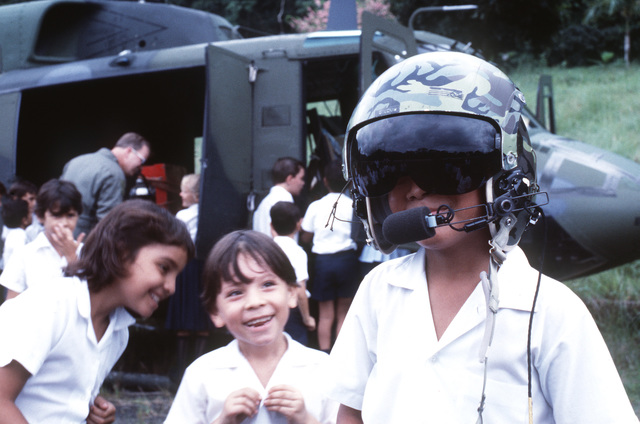 A Costa Rican boy tries on a flight helmet as other children study a Detachment 1, 1ST Special Operations Wing UH-1N Iroquois helicopter which is being used to transport personnel for civic action projects