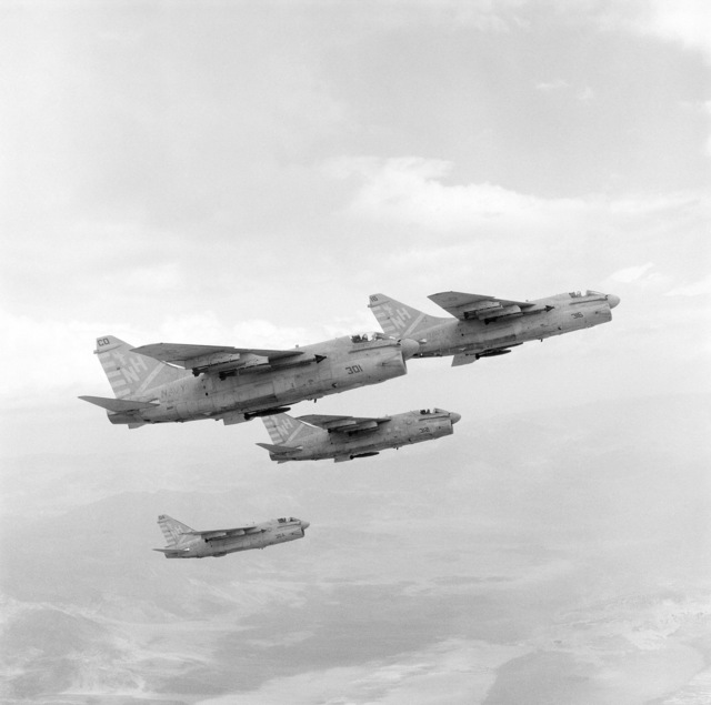An air-to-air right side view of three A-7E Corsair II aircraft of Attack Squadron 22 (VA-22) carrying AIM-9 Sidewinder missiles and Mark 82 500-pound bombs.  The aircraft are en route to a target range at Naval Weapons Center, China Lake