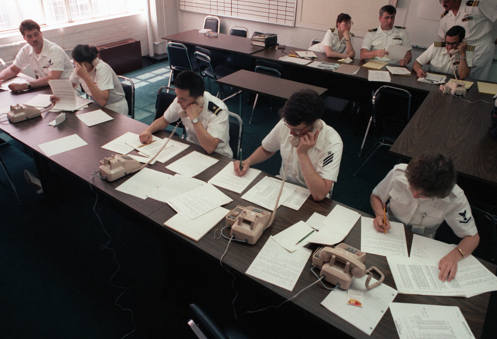 US Navy personnel take calls at the Emergency Coordination Center regarding the guided missile frigate USS STARK (FFG 31).  Thirty-seven crew members were killed aboard the STARK when it was struck by two Irqi-launched Exocet missiles in the Persian Gulf on May 17, 1987