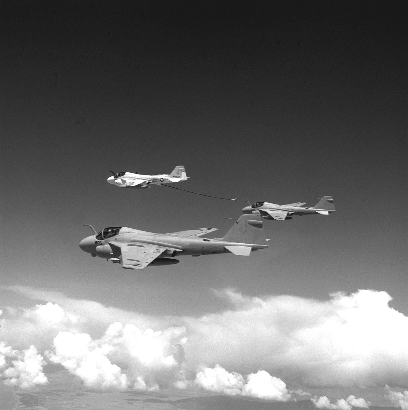 An air-to-air left side view of two Attack Squadron 34 A-6E intruder aircraft preparing to refuel from an Attack Squadron 60 (VA-60) KA-6D Instruder aircraft over Naval Air Station, Fallon, during Carrier Air Wing 7 (CVW-7) strike training