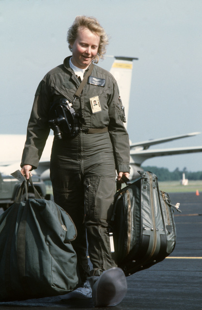 Captain (CPT) Kim Schmidt of the 171st Air Refueling Wing, Pennsylvania Air National Guard, carries her bags from the KC-135E Stratotanker aircraft to the squadron operations building where she can change out of the chemical warfare gear during Exercise KEYSTONE BADGER