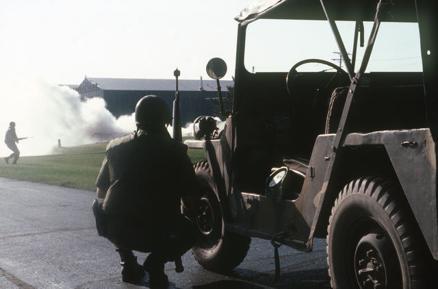 Members of the 171st Security Police Force, Pennsylvania Air National Guard, defend the flight line during Exercise KEYSTONE BADGER.  The smoke in the background simulates a blown-up hangar