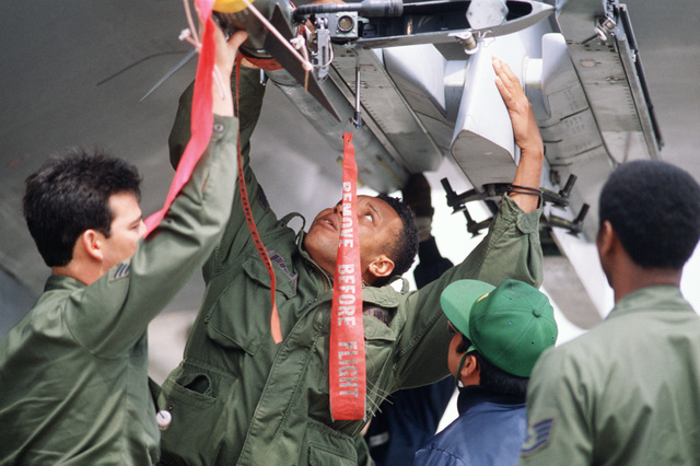Sergeant (SGT) William Brown, center, works with other members of the 18th Aircraft Generation Squadron and Japan Air Self Defense Force 2nd Wing to remove a missile from the wing of a 44th Tactical Fighter Squadron F-15 Eagle aircraft during Exercise COPE NORTH'87-3