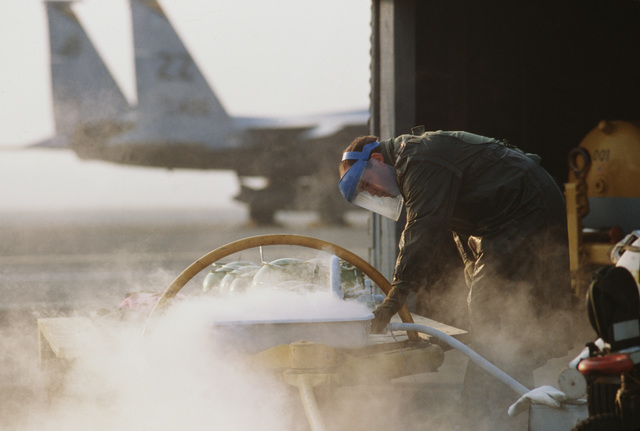 STAFF Sergeant (SSGT) Rick Whittaker, 18th Aircraft Generation Squadron, services liquid oxygen converters on the flight line while an F-15 Eagle aircraft from the 44th Tactical Fighter Squadron taxis by during Exercise COPE NORTH'87-3