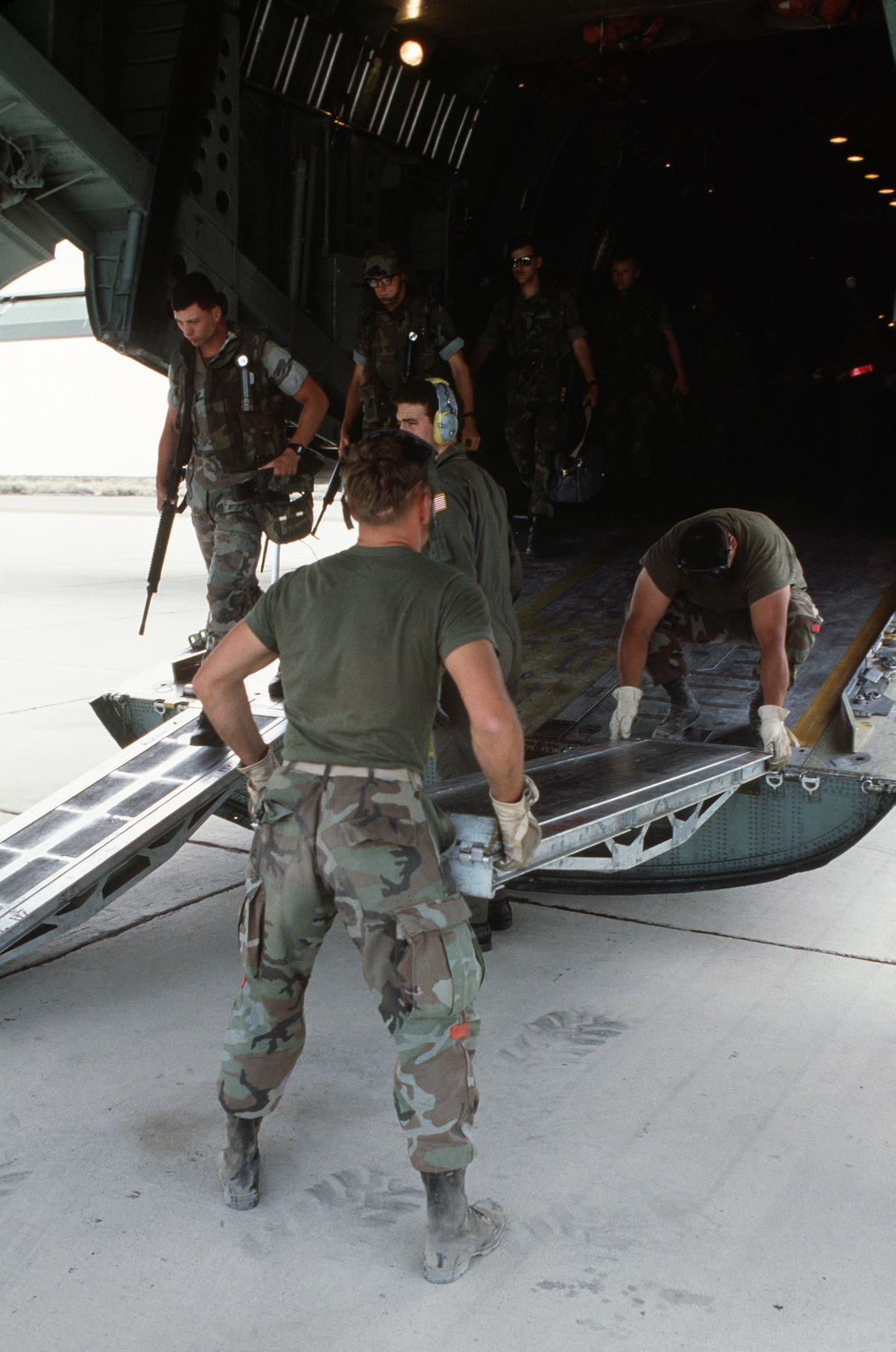 Air Force ground crewmen assemble a boarding ramp as Marines march out the rear cargo doors of a C-141B Starlifter aircraft during a joint Air Force/Marine Corps exercise.  Members of the Air Mobile Contingency Force, 2nd Battalion, 9th Marines are working with members of the Air Force's 63rd Military Airlift Wing to airlift Marines and 737 tons of vehicles, supplies and equipment to China Lake Proving Grounds for field maneuvers