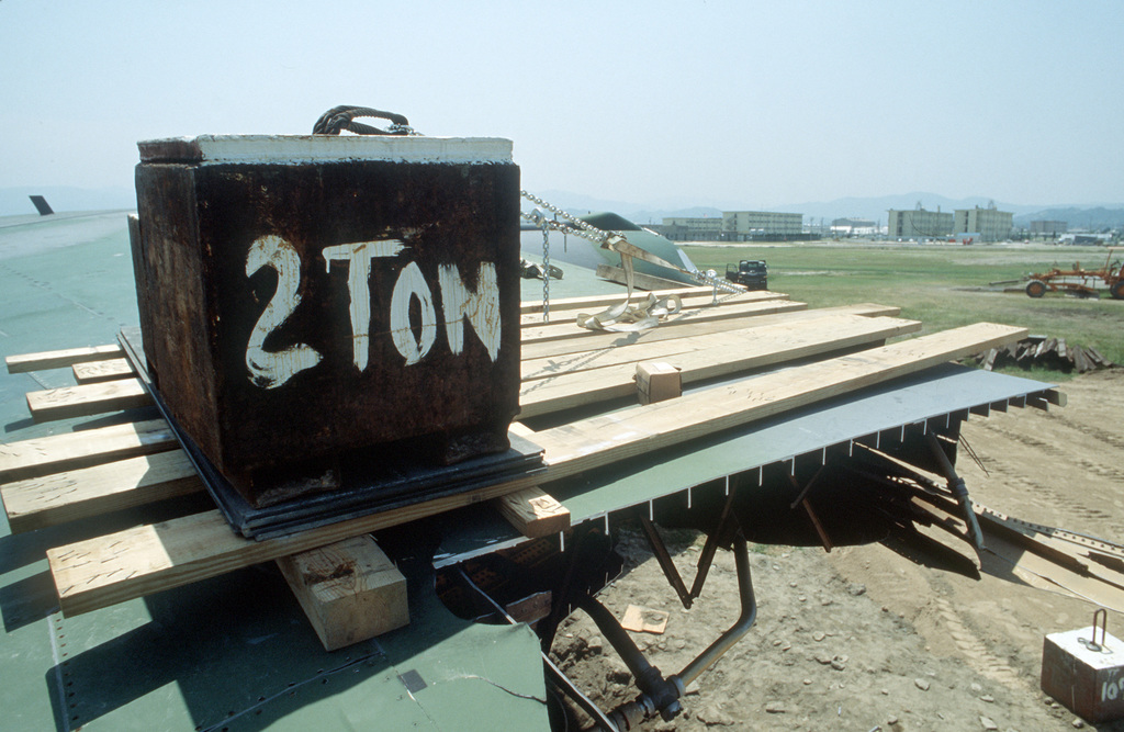 A platform and weight atop the right wing of a C-141B Starlifter aircraft provide a counterbalance as members of the 2955th Combat Logistics Support Squadron prepare to move the plane to a new parking position for eventual repair.  The aircraft was damaged when it slid off the runway after landing on the airfield