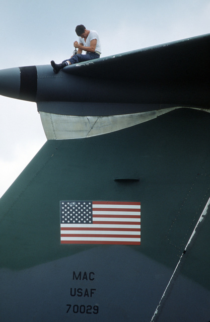 STAFF Sergeant (SSGT) Bob Weaver, 2955th Combat Logistics Support Squadron, removes an emergency locator transmitter atop the vertical stabilizer on a C-141B Starlifter aircraft.  The aircraft was damaged when it slid off the runway after landing on the airfield, is being moved to another parking position for eventual repair