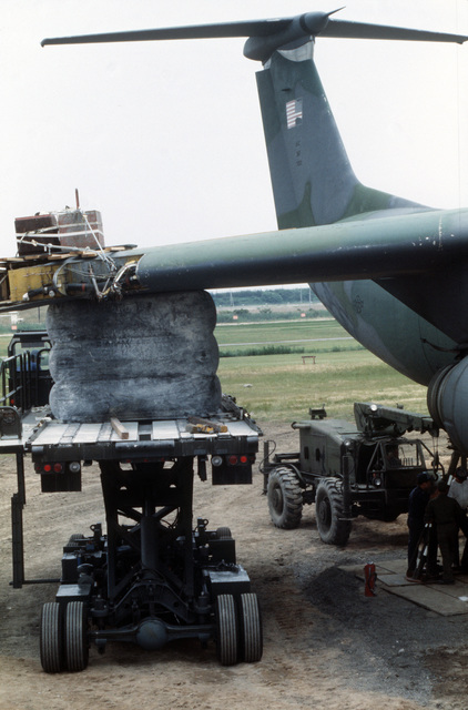 Using K-loaders, airbags are placed under each wing of a C-141B Starlifter aircraft to provide stability as the aircraft is moved to a new parking area for eventual repair.  The aircraft was damaged when it slid off the runway after landing on the airfield