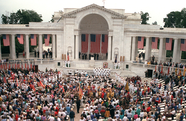 Military personnel and civilians gather in the outdoor amphitheater for Memorial Day observances at Arlington National Cemetery
