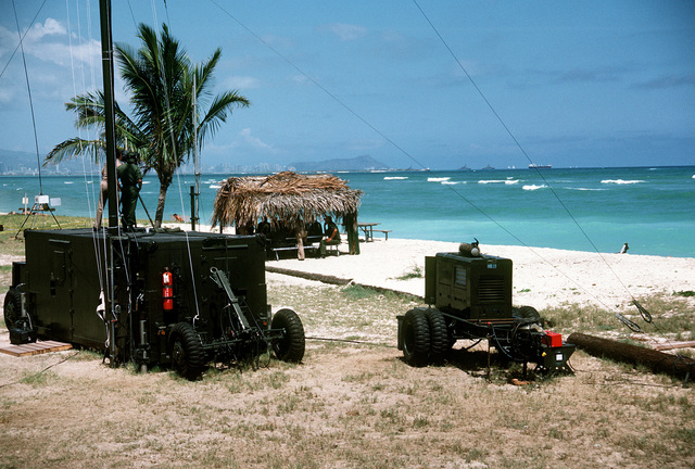 A mobile communications van and an MB-19 generator set stand on the beach during inshore undersea warfare operations