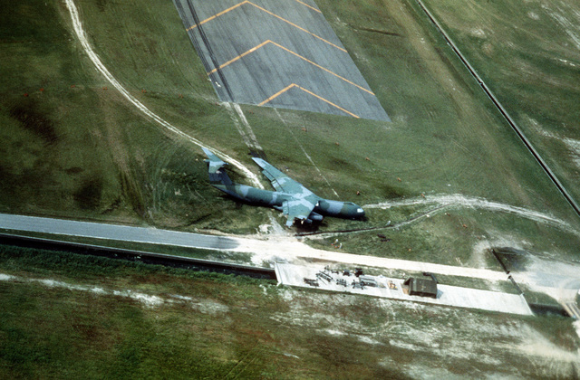 Aerial view of a 63rd Military Airlift Wing, Norton Air Force Base, California's C-141 Starlifter that was damaged when it ran off the end of the runway at Marine Corp Air Station Iwakuni, Japan. Both landing gears were torn off, the fuselage sustained heavy damage and fire destroyed half of the right wing. Exact Date Shot Unknown