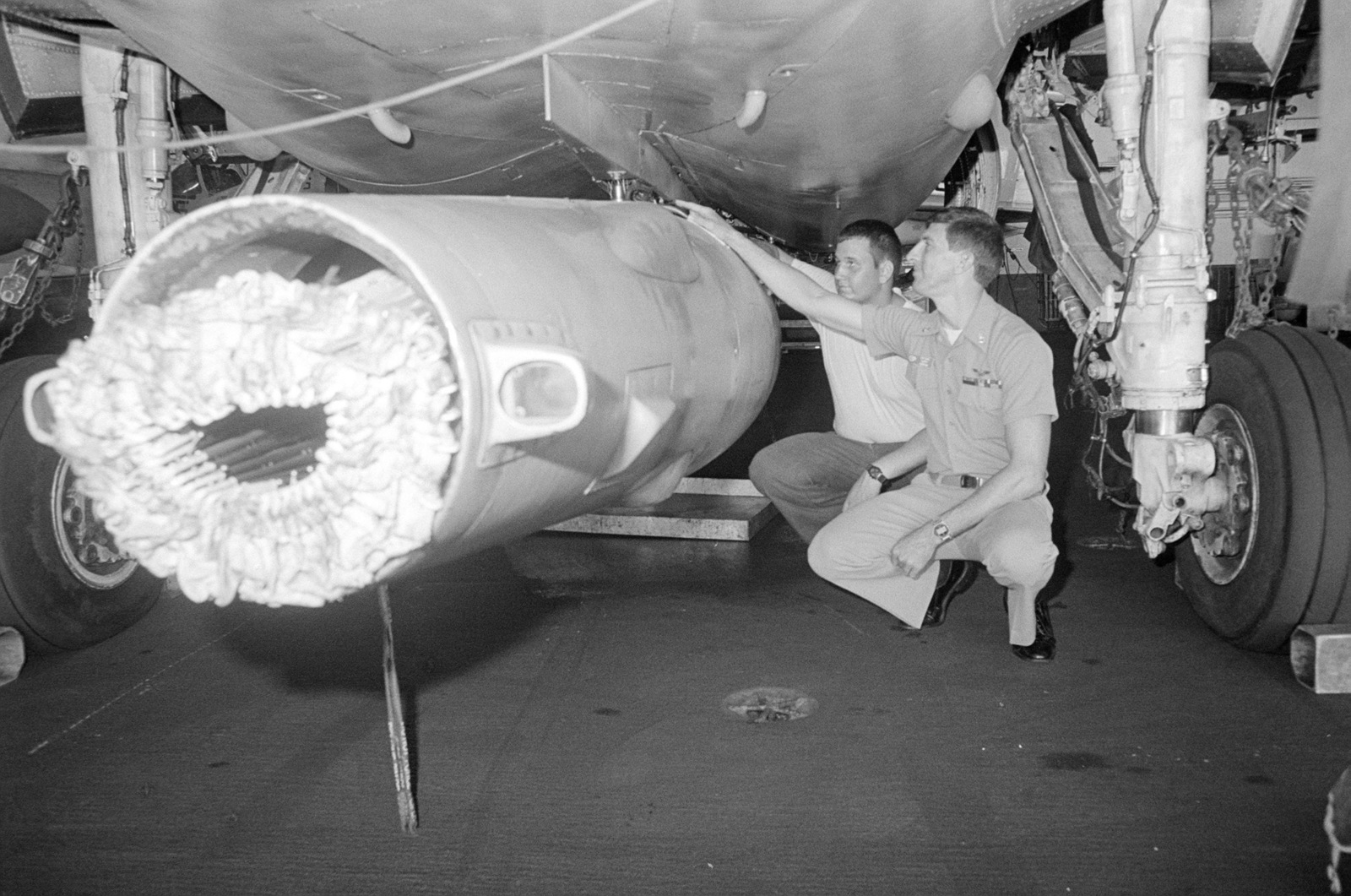 CHIEF Aviation Machinist's Mate Larry Hanson inspects an aerial refueling unit attached to the centerline of an A-6 Intruder aircraft. The A-6 is in the hangar bay of the aircraft carrier USS KITTY HAWK (CV 63)
