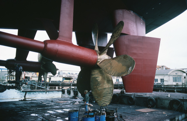 Shipyard workers examine the newly polished props and painted shafts of the fast combat support ship USS SACRAMENTO (AOE 1).  The ship is undergoing regular overhaul in a floating dry dock at the National Steel and Shipbuilding Company shipyard