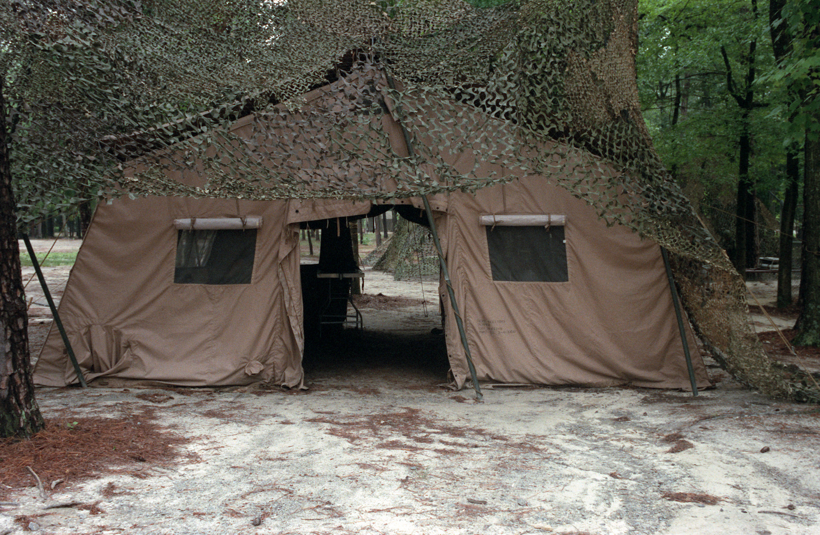 An exterior view of a camouflaged M-1948 kitchen tent  The tent is a
