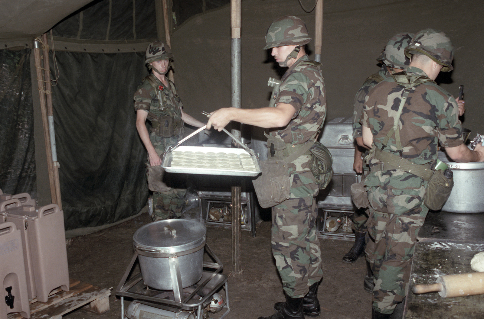 Soldiers prepare biscuits inside an M-1948 kitchen tent  The tent is