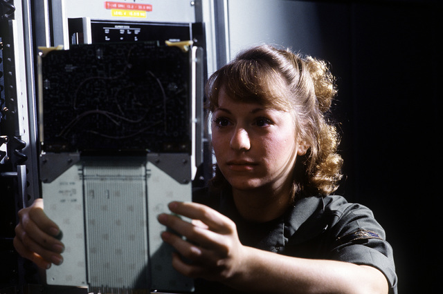 AIRMAN 1ST Class Julie Berry, a ground radio communications specialist of the 2006th Information Systems Group, inspects a channel A IF card used in radio transmitters