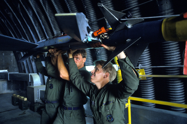 AIRMAN First Class (A1C) James Waara and other weapons load crew members load an AIM-9 Sidewinder missile on an F-16 Fighting Falcon aircraft