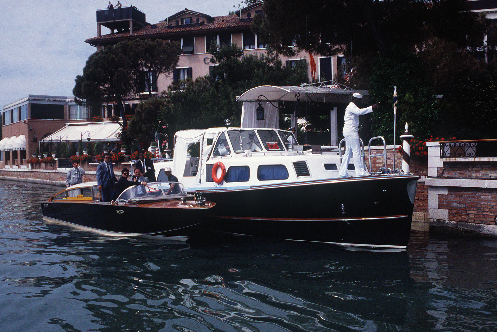 an italian water taxi and a us navy barge provide security for