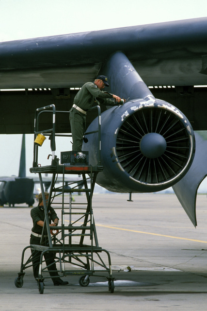 Staff Sergeant (SSGT) Jimmy Olson adds oil to a C-141B Starlifter engine