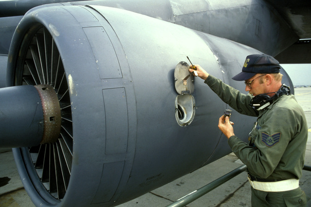 Staff Sergeant (SSGT) Jimmy Olson checks and services the oil in a C-141B Starlifter engine